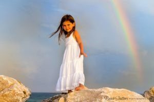 Girl on rocks at the beach with Rainbow in the background