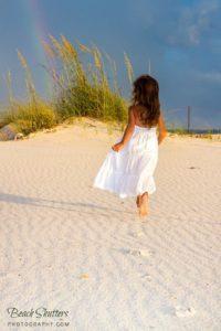 Young girl ruining on the beach towards the Rainbow.