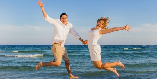 Couple on the beach jump up for a fast action portrait in Orange Beach www.beachshuttersphotography.com