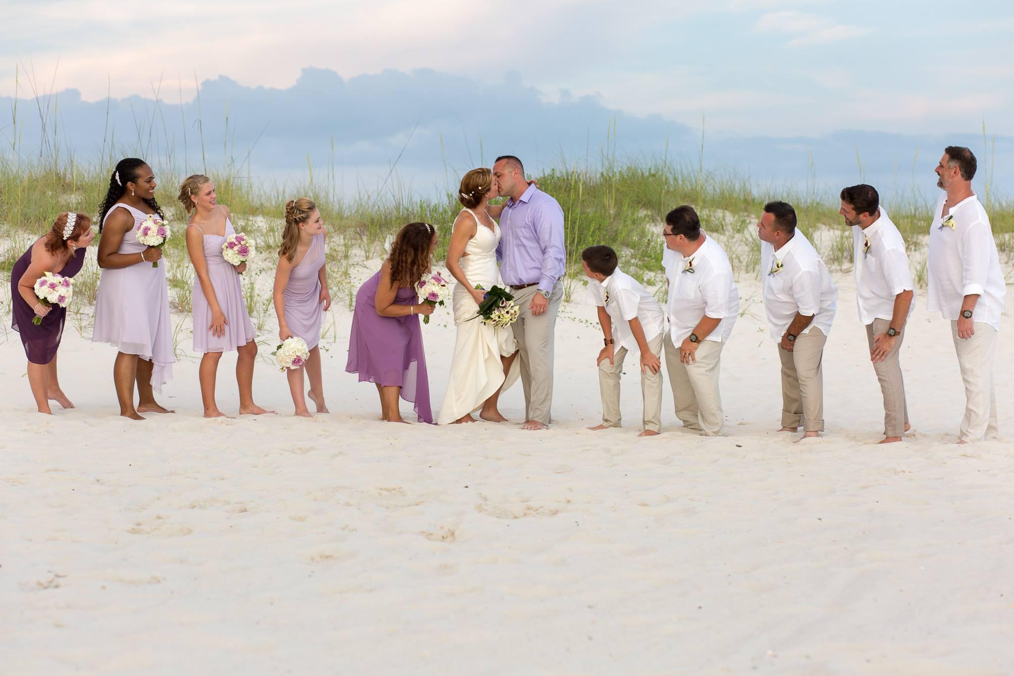 Perdido Beach Resort wedding. Wedding party observing the big kiss on the beach in Orange Beach al