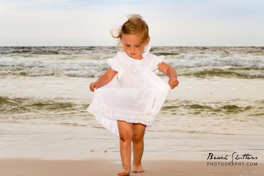 baby in white gets wet during photo session in Orange Beach
