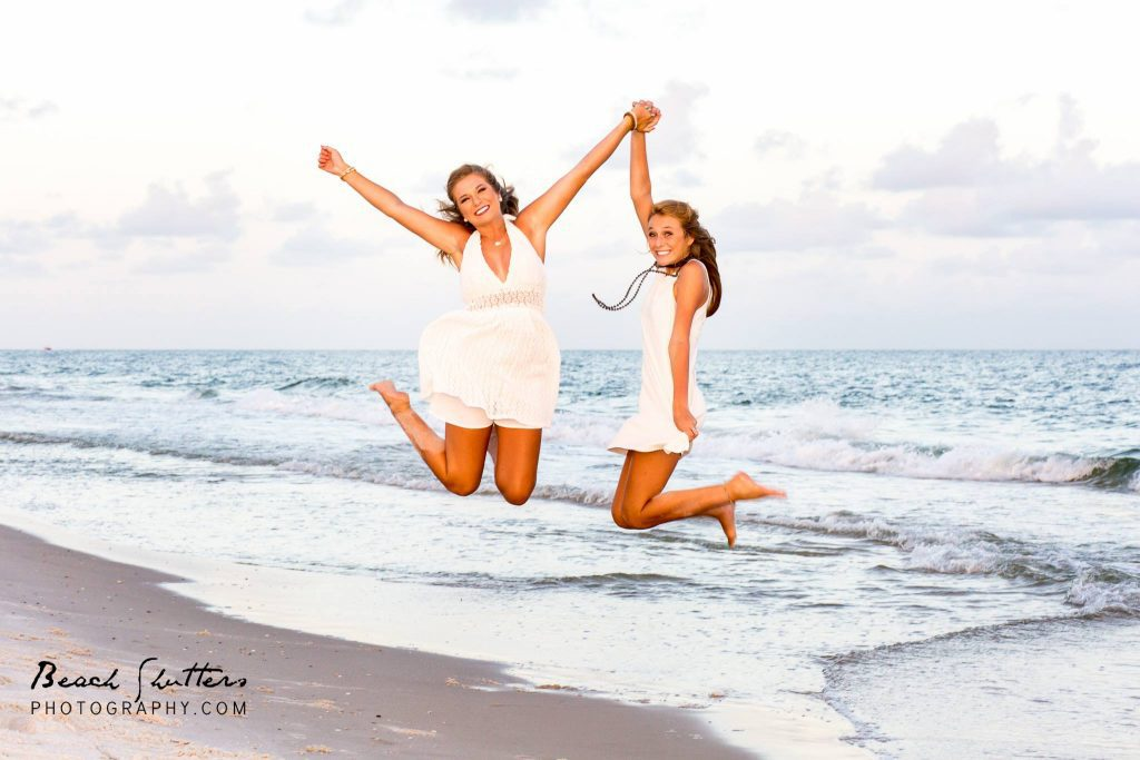 sisters jumping for joy at the beach