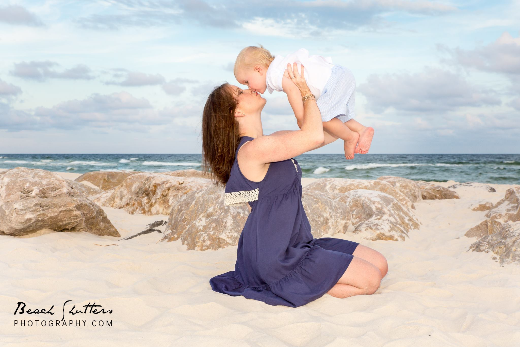 kisses for mom in a cute photo at the beach in Gulf Shores