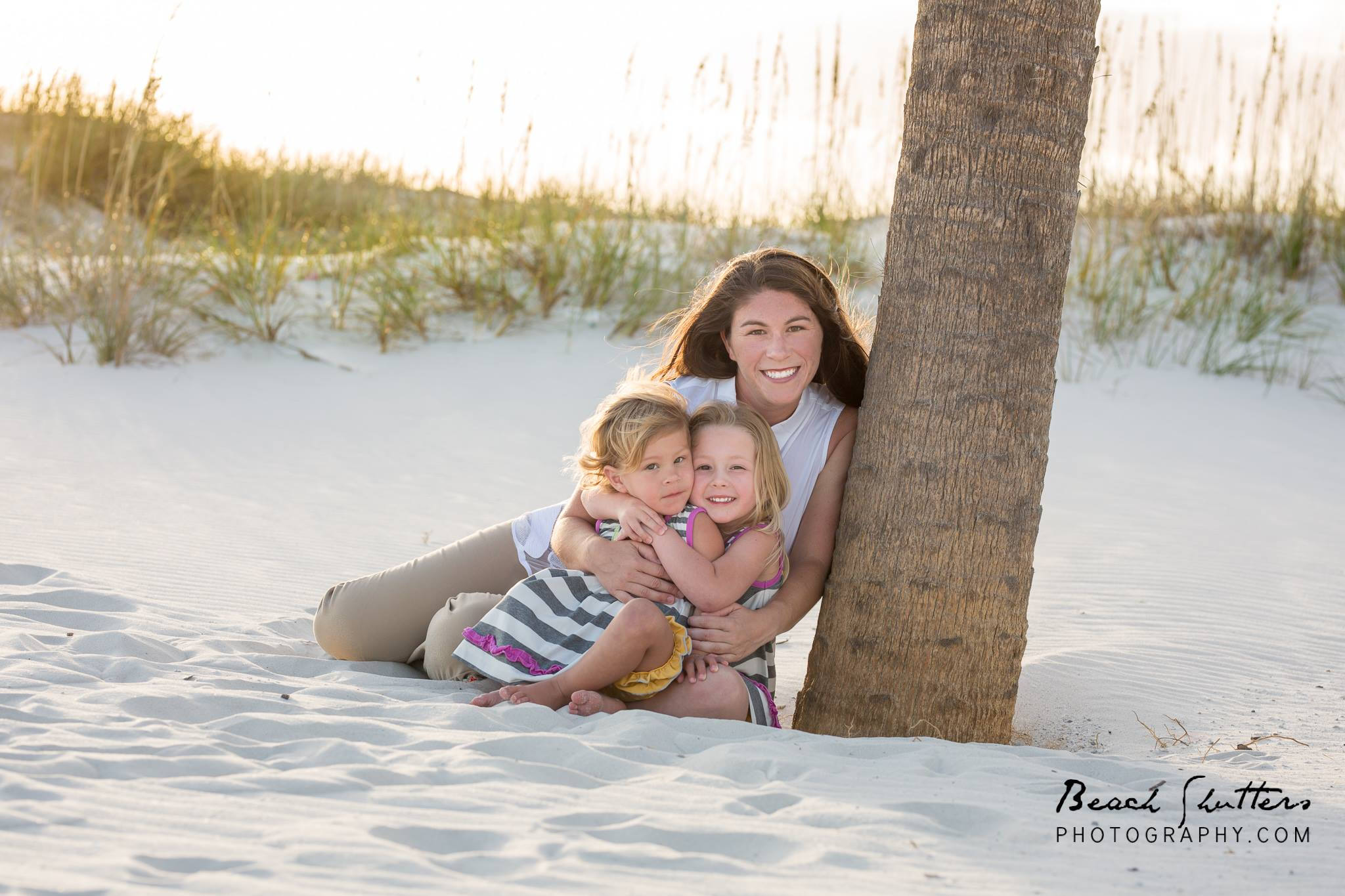 Mother and 2 daughters snuggled up by a palm tree in Fort Morgan Al